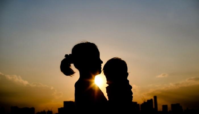 夕陽を背景に子どもを抱く母親