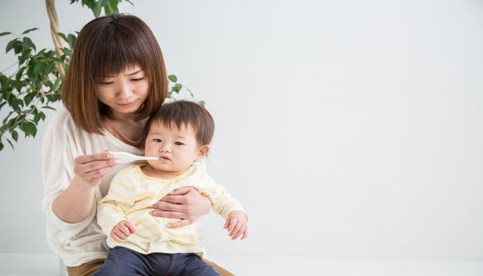 子どもを抱きながら体温計を見る母親